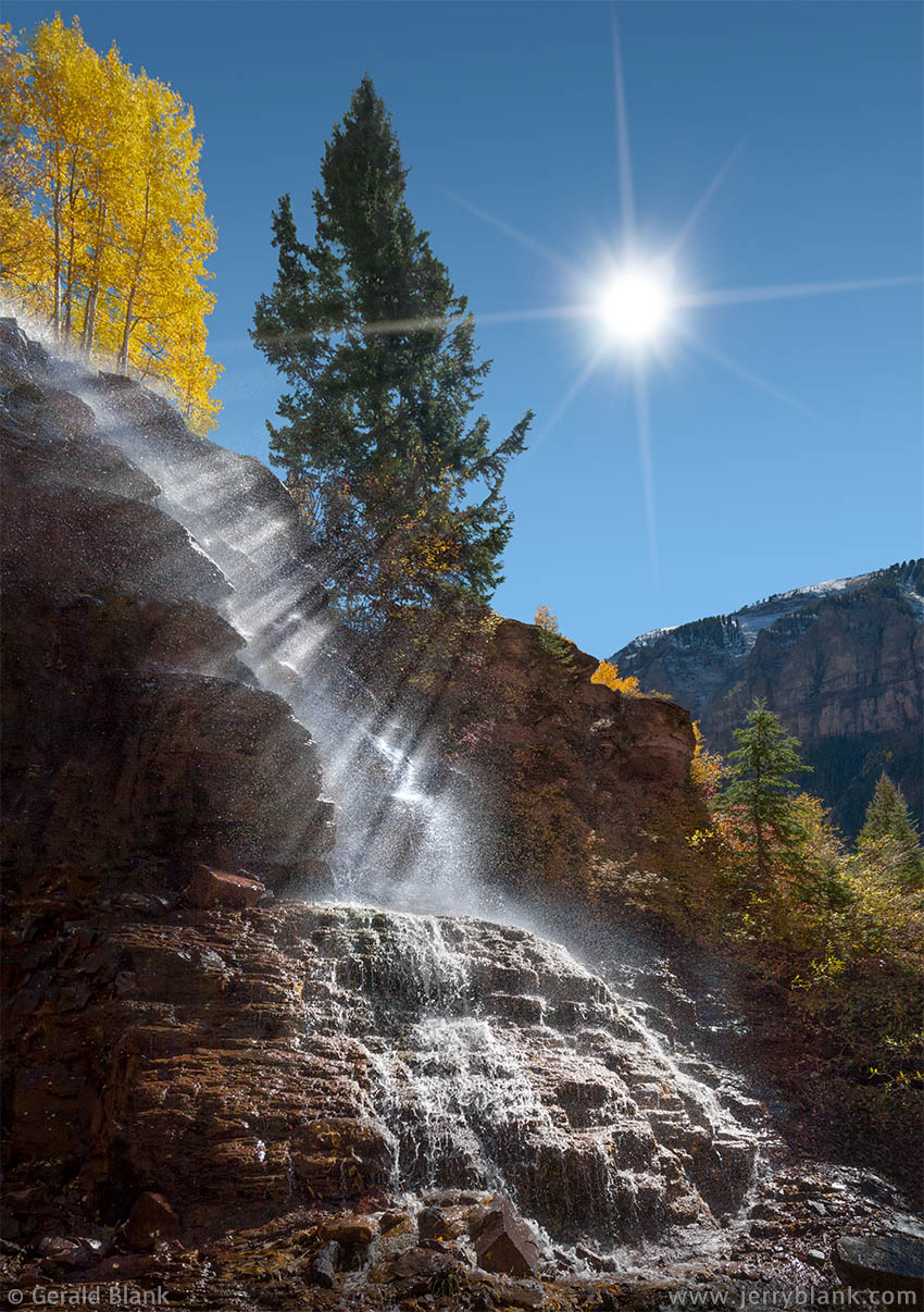 #06918 - Water sprayed from a flume above Marshall Creek is caught by the rays of the sun, outside of Telluride, Colorado - photo by Jerry Blank