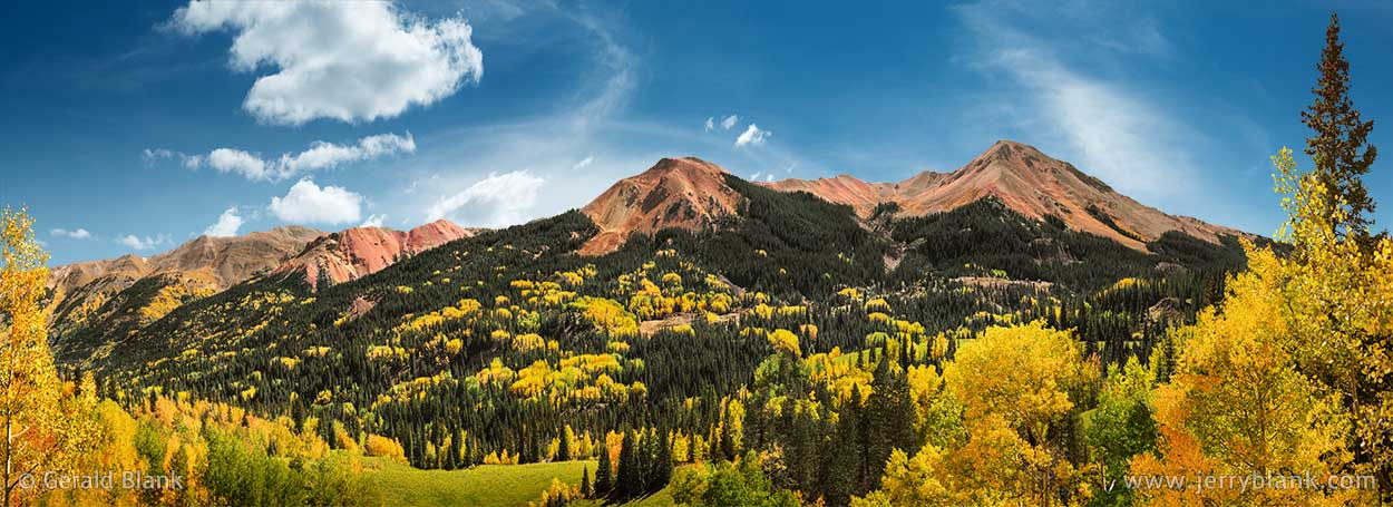 "#45420 - An autumn aspen panorama of the three ""Red Mountains"" in Colorado, north of Red Mountain Pass. The Idorado Mine is visible at the base of the mountains - photo by Jerry Blank"