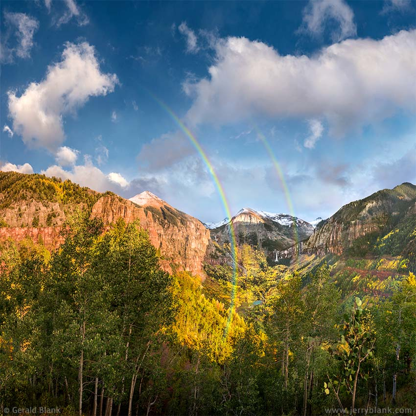#49450 - A double rainbow lights up the San Miguel canyon east of Telluride, Colorado. Ajax Peak, Ingram Falls, Ingram Peak, and Bridal Veil Falls are visible in the distance - photo by Jerry Blank